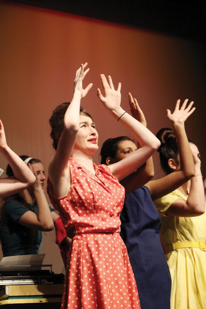"""ACting — Senior Crosby Dold reaches up during a scene in the winter musical, """"How to Succeed in Business Without Really Trying."""" Dold plans to study theater in college."""