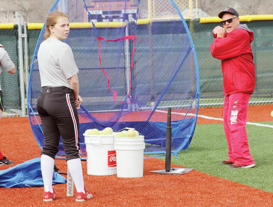 Demonstrating+how+to+swing+the+bat%2C+coach+Joe+Dee+Tarbutton+helps+sophomore+Katie+Murrish+during+softball+practice.