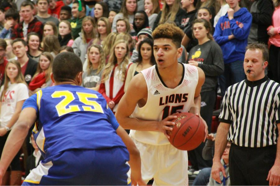 Leading his team to a win over Olathe South, senior Anthony Bonner looks to pass the ball during the Jan. 9 home game. Bonner scored 23 points and had five rebounds.