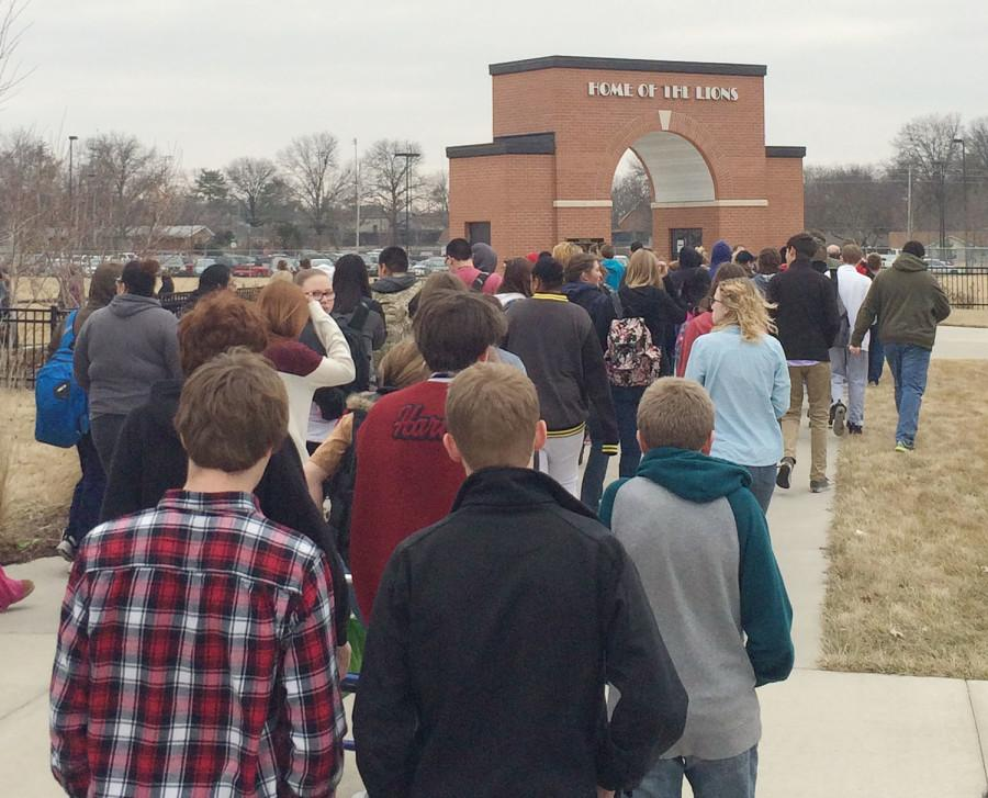 Students walk away from the football stadium and toward the West Gym after the school was evacuated on Wednesday afternoon.