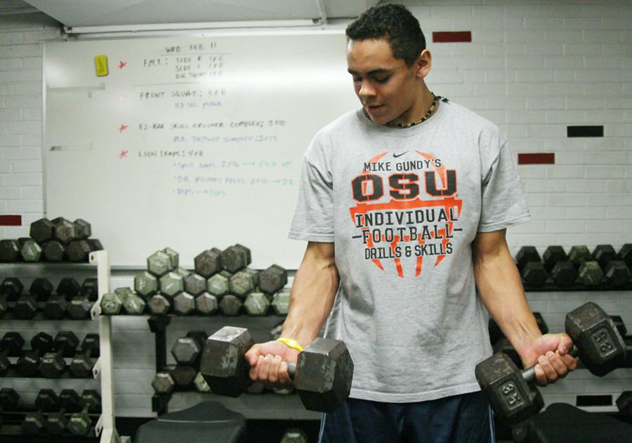 Sophomore Trey Moore  lifts weights during class on Thursday.