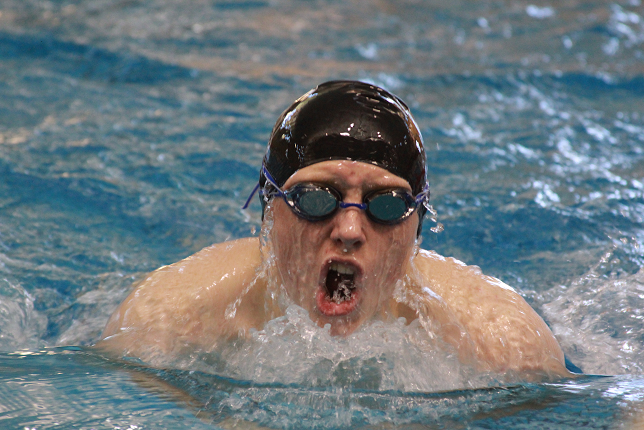 Swimming breast stroke at a home meet in January, junior Chase Odgers was part of the varsity swim team that took 11th at state. Juniors and seniors benefited from a new group of talented freshmen.