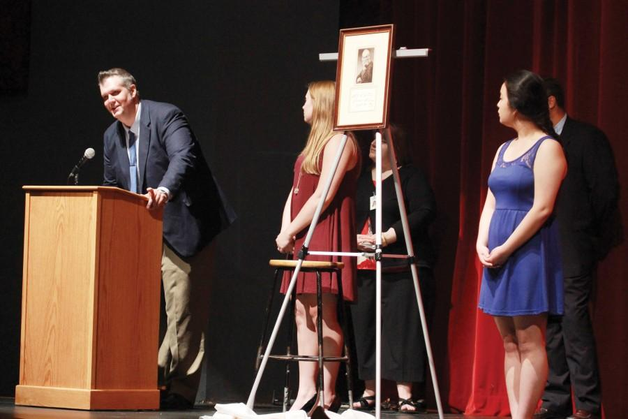 "Looking on as Michael Carriger speaks, senior Joo-Young Lee helps present the senior class gift during senior awards night. ""It was an honor to present our unique senior class gift on such a special and memorable night,"" Lee said."
