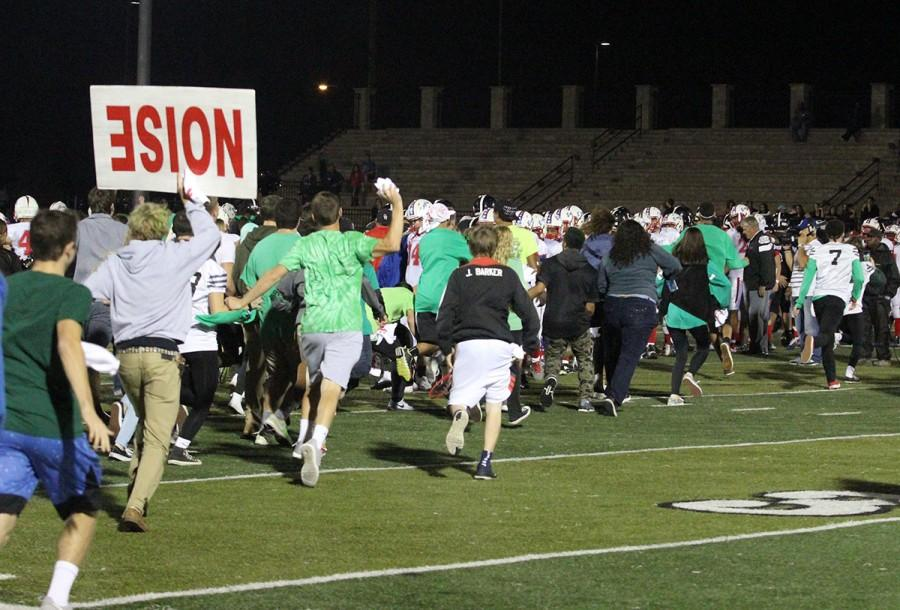 Fans rush the field after the Lions clinch a close victory against Olathe North on Oct. 23.