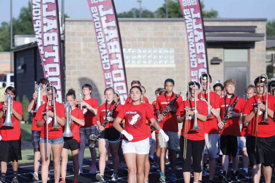 Senior Mia Franklin leads the marching lions onto the field for their first marching performance of the school year.