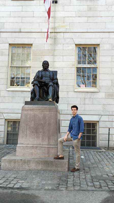 "Senior Stefan Petrovic poses with a statue of the founder, John Harvard, on the Harvard University campus. Petrovic notes that the right toe of the statue is worn gold due to tradition. ""Visitors like to rub it for good luck, but they are often unaware that by the time they graduate, nearly every Harvard undergrad has urinated on the statue, so I chose to not touch the foot,"" he said. Photo courtesy of Stefan Petrovic."