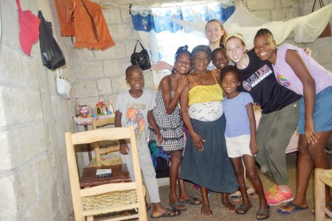 "Coming together — Junior Claire Walther poses with her and junior Tia Herrman's family in Haiti. ""We had just finished doing a dance circle and it got really dark,"" Walther said. ""We got the camera out and did a little night photo shoot, which the kids really enjoyed."""
