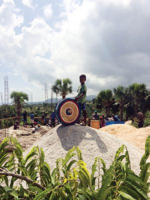 "To the beat — A Haitian child drums while villagers and students work on constructing a new school in the village of Abraham. ""They would play and occasionally dance along while we were working,"" junior Quentin Harrington said."