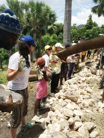 "On the Line — Volunteers work at a rock line to help create the foundation for the school in Haiti. ""It was really fun because as we were passing the rocks they taught us different words in Creole,"" Harrington said."
