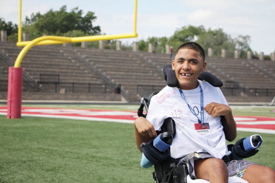 Smiling gleefully — Junior Travis Barfield sits on the football field for a photo. Barfield led the varsity football team onto the field Sept. 9 as the game's honorary captain. Barfield played on the team before his heart stopped in January while he was out for a run.
