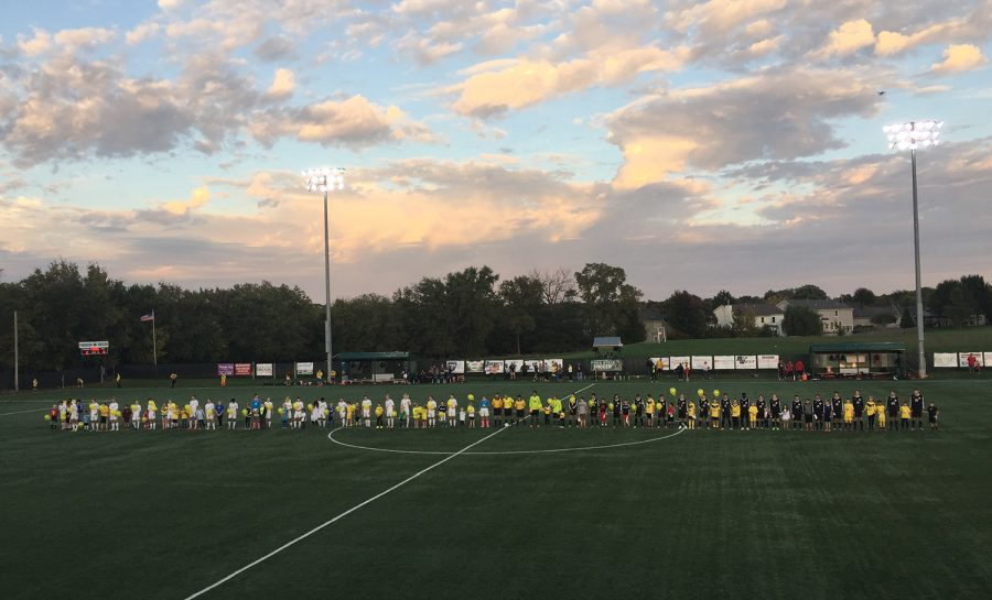 Members of the Free State and LHS soccer teams wore yellow on the field before the start of the Oct. 10 game to honor Amanda Kapfer, the parent of two Free State soccer players. She had died of cancer a few days before the game, and the teams wanted to honor her memory.