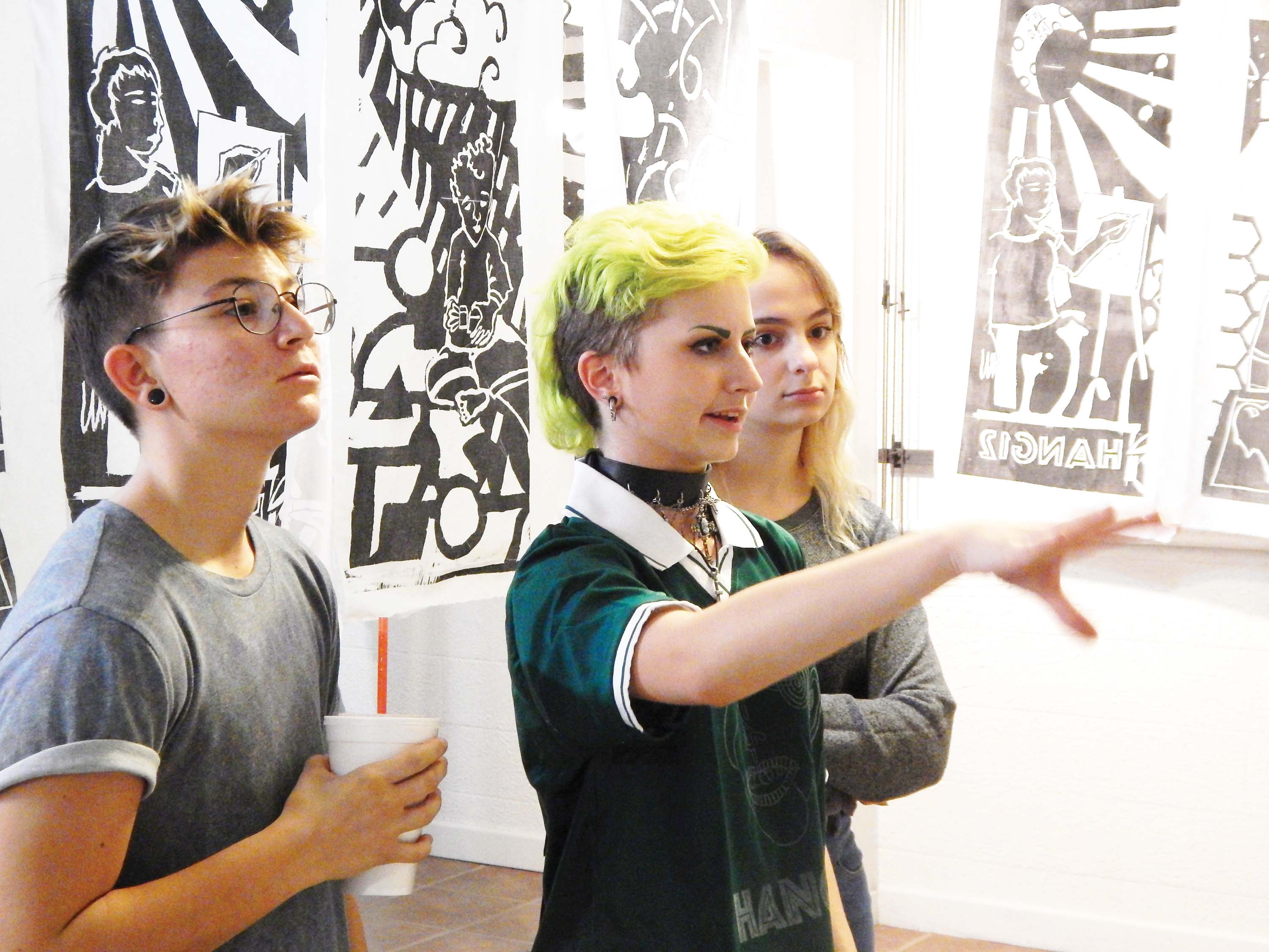 Observing the Art — Senior Toby Weston explains a woodblock carving that Hang12 members made for a recent show to junior Mia Romano and sophomore Olivia Rothrock.