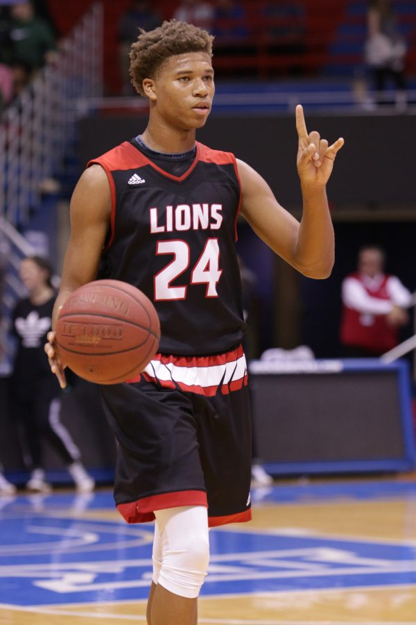Sophomore guard Clarence King brings the ball up court, calling out a play during the game against Free State. The Lions won 61-57 during the matchup at Allen Fieldhouse last week.