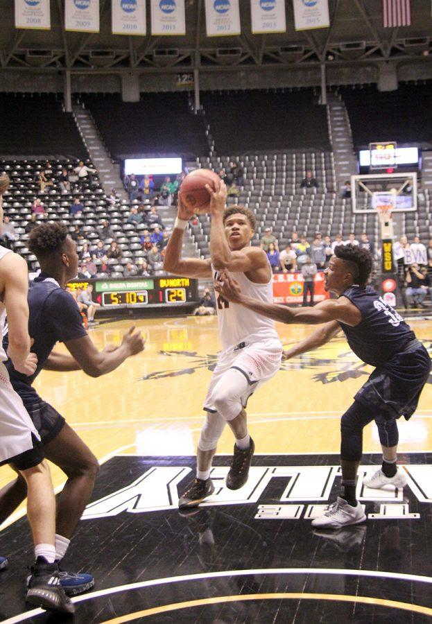 Sophomore Clarence King drives to the basket during the state semifinal win on Friday night. King led scoring with 17 points.