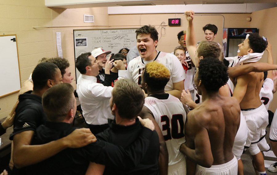 Senior Kobe Buffalomeat (center) and other members of the basketball team celebrate their state semifinal win the locker after Friday's game.