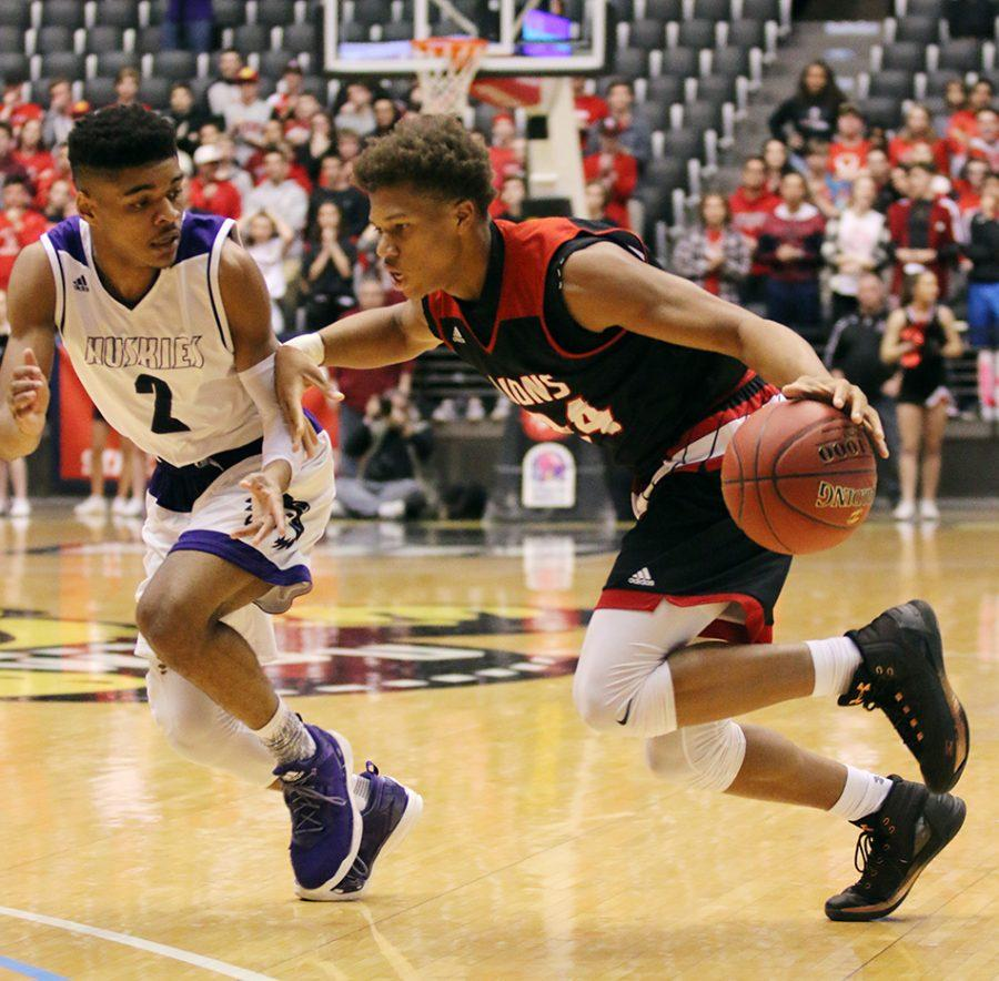 Taking the ball down the court, Clarence King dribbles under pressure from BVNW player Anthony Pleasant during the first half of the state basketball tournament championship game.