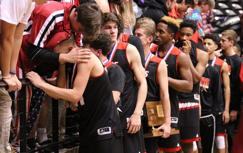 Senior DJ Davis embraces senior Jackson Mallory as he comes off the court after the Lions fell just short of a state title. LHS mounted a late comeback against Blue Valley Northwest in the state championship game before losing 64-61.