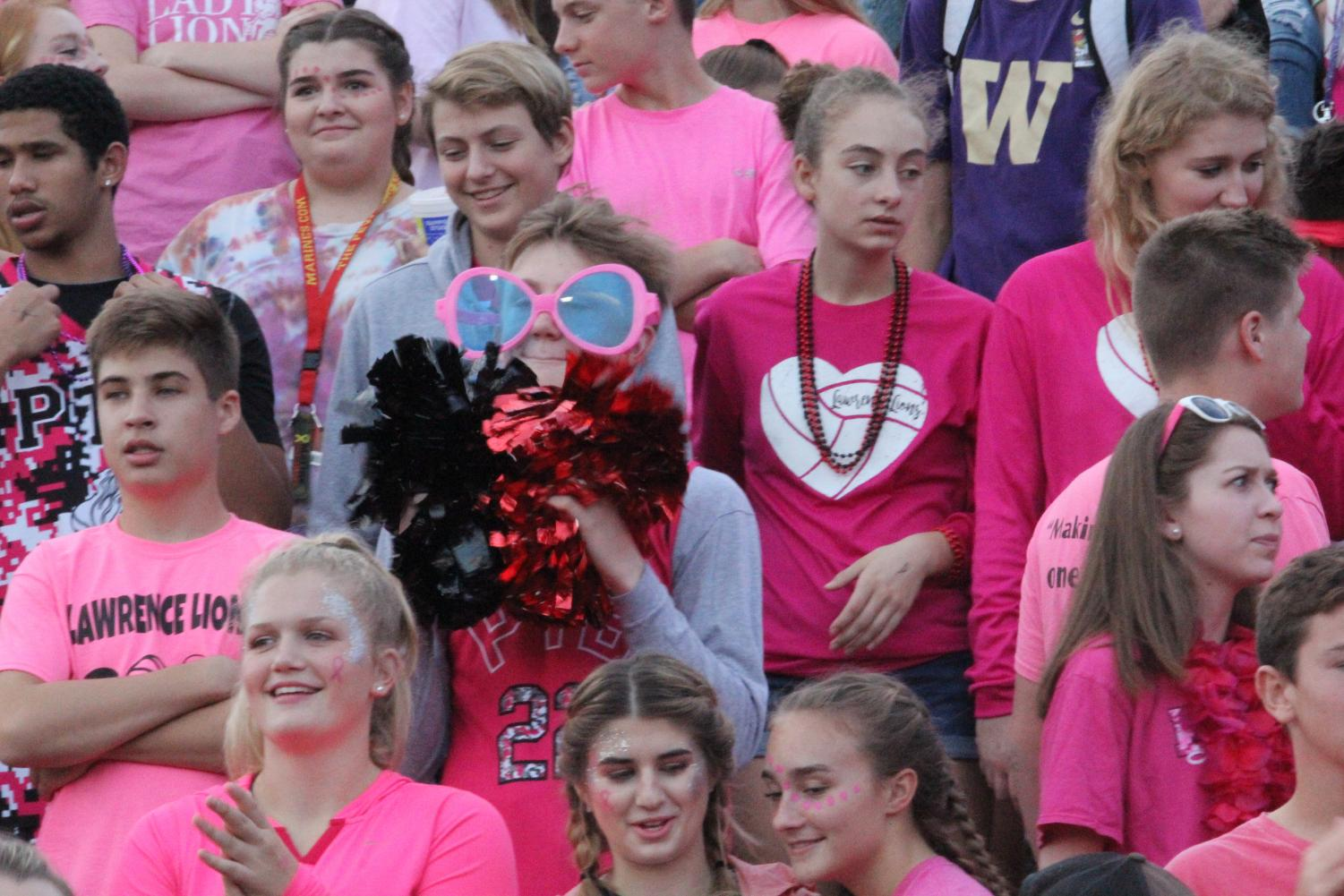 """PRETTY IN PINK — Sophomore Melanie Meyer is spotted in a sea of pink as Lawrence High celebrates the annual pink-out game. """"I enjoyed the game,"""" Meyer said. """"Football is a good time for people to come together and just have fun."""""""