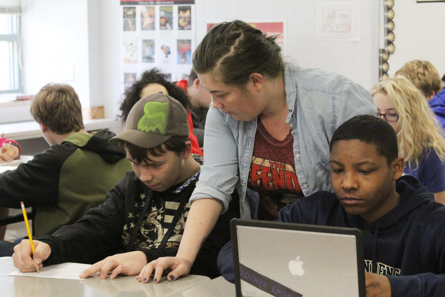 Helping Hand— Paraprofessional Jennifer Stock helps freshmen students work in English class.