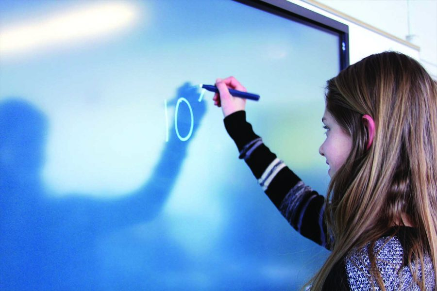 Solving the equation — Junior Adelai Spears uses the new smart board in math teacher Greg Farley's classroom. The new update comes as a sneak peak to what all the classrooms at Lawrence High will look like after the school renovation.
