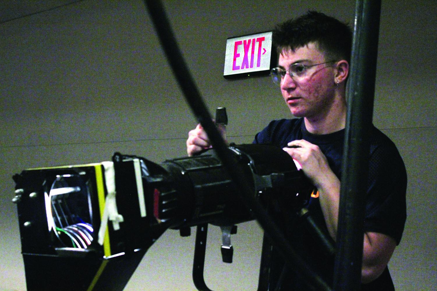 Adjusting — Senior Liam Romano runs the lights in his position at the Lawrence Arts Center.