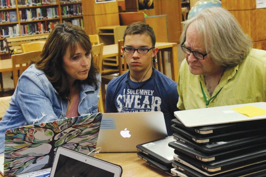 Junior Chris Kogan gets help from Rachel Smith and Steve Wilson, who work tediously through stacks of laptops to get them all checked out and running as soon as possible. Wilson said it took a lot of work and lacked some organization but is confident that next year the process will run smoothly.
