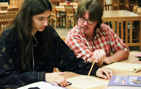 """Paraprofessional Quinton Cheney helps senior Ray Haskett work through a test for Haskett's Senior Consumer Math class. """"I get to bounce around between subjects,"""" Cheney said of his job as a para. """"I get to learn from teachers while I help the students. It can be very humbling."""""""