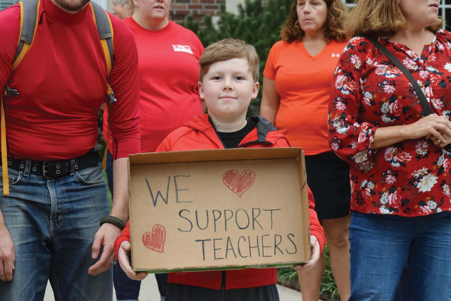 """Supporting the cause, community members of all ages gather to support teachers on Sept. 6 outside Liberty Memorial Middle School. Parents, teachers and students from across the district stood together on what was supposed to be Liberty's open house night, a night teachers aren't specifically paid to attend. """"It's a hard place to be when you're a teacher, because they care so much about our kids, their jobs and their professions and doing what's right,"""" said Jenny Skillman, the leader of the initiative."""