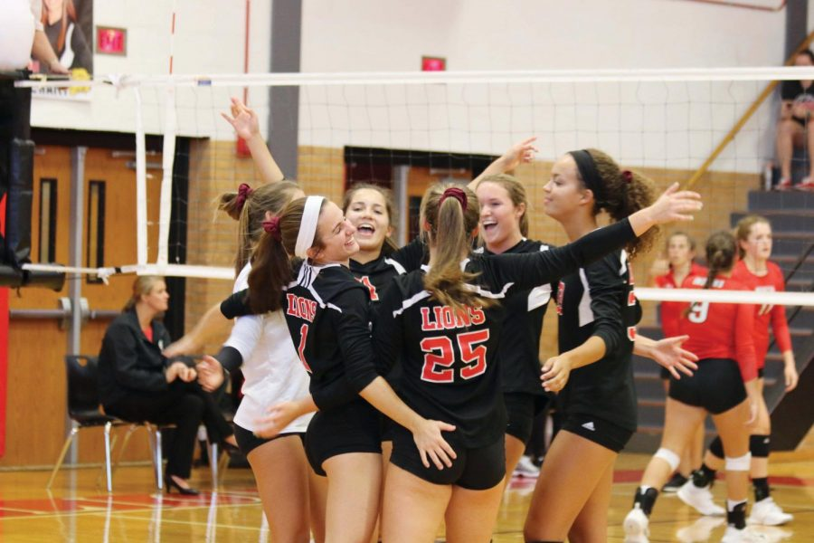 The Volleyball team celebrates after scoring a point against Shawnee Mission North on  Sept. 11. The Lady Lions won the match two sets to none (25-8, 25-9).