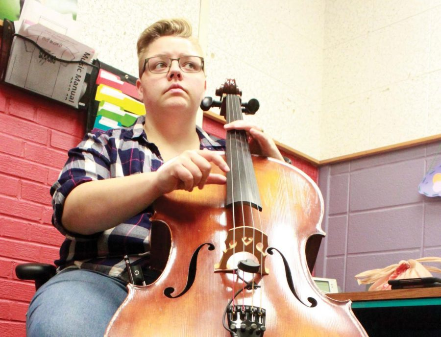 "Playing the cello while using the loop pedal, Mrs. Mariah Barnett demonstrates how she uses the device to accompany herself. The new orchestra teacher busks about six times a year on mass street and at the lake. ""I'll busk about four times just at the lake for the campground"" Mrs. Barnett said. ""thats mostly to perform for my family and friends."""
