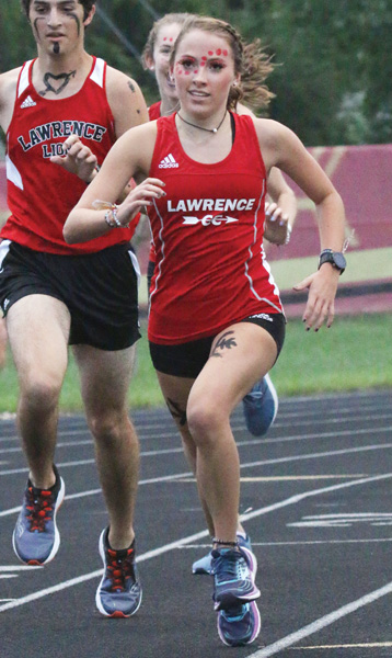 At Jamboree in August, junior Maiki Martinez runs around the track with other members of the cross country team, which she joined after transferring from Baldwin High School.