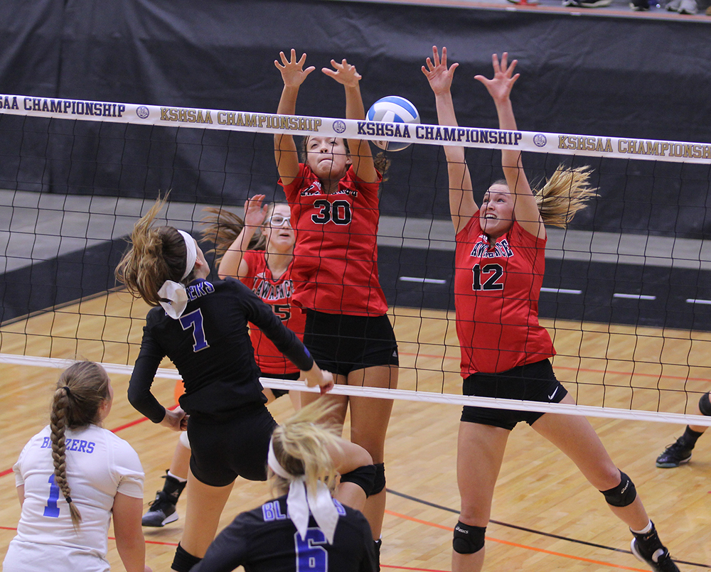 Seniors Abby Monroe and Brooke Wroten reach for the ball during the state volleyball tournament on Friday in Salina. The Lions beat Gardner-Edgerton in two sets.
