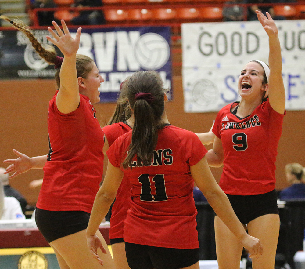 Hannah Stewart leaps with other members of the LHS volleyball team as they near the end of their second set against Blue Valley High School. The Lions dominated the first day of play at the state tournament in Salina.