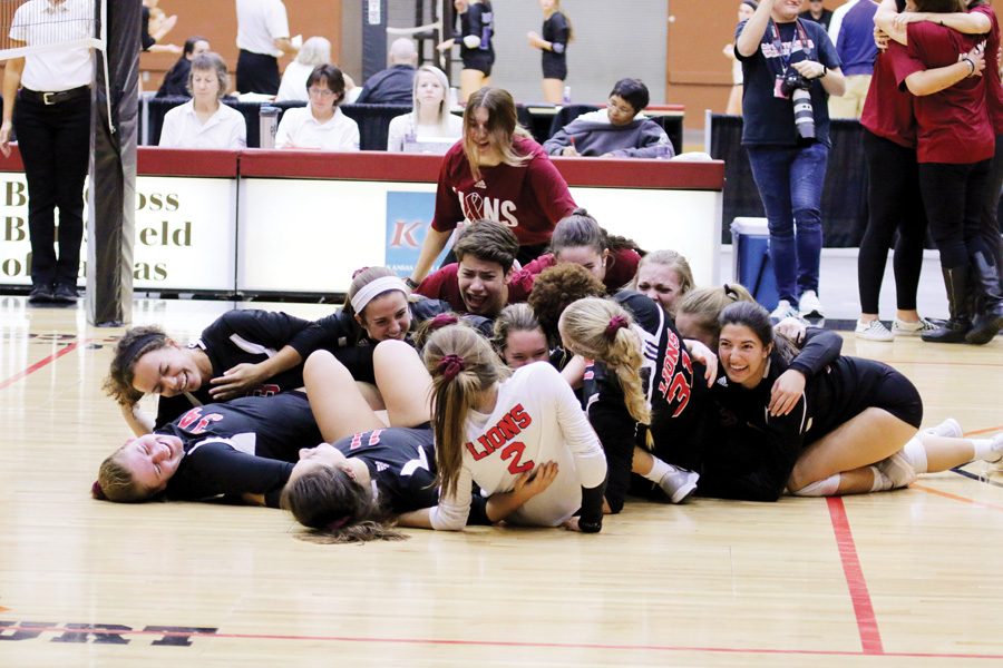 The volleyball team celebrates in a dogpile after winning the final point of its match to be named 6A state champions during the state tournament in Salina.