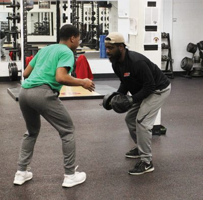 Security guard and assistant football coach, Jeff Colter works on a footwork drill with junior Deshon Lewis in the weight room after school.