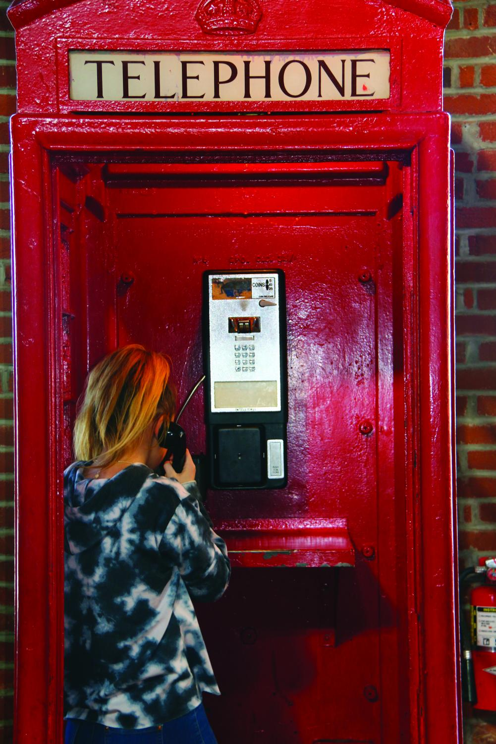 """unior Tessa Norcross stands in the telephone booth at Abe and Jakes Landing. This year, the Winter Formal dance is set to take place at Abe and Jakes Landing. """"It was cool,"""" Tessa said."""