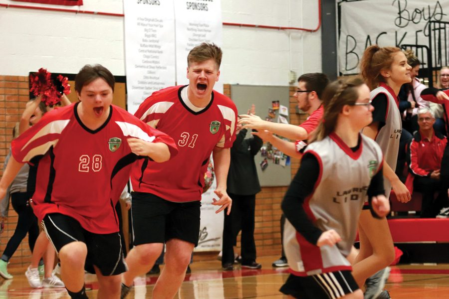 juniors Alan Sanders and Bryce Smith celebrate after making a basket in the Unified Sports scrimmage at Pack the House on Nov. 19. Unified Sports is one of the activities featured in Pack the House that currently cannot receive a letter. Students involved have been advocating for their lettering privileges.