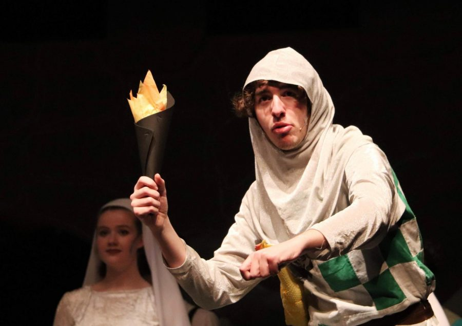Holding a torch, junior Noah Stussie rides an imaginary horse during the winter musical, Monty Python's Spamalot on Jan. 25. Stussie was a knight of the round table and accompanied King Arthur on his quest to find the Holy Grail.