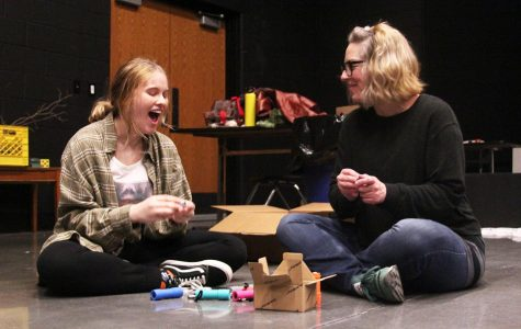 Smiling, junior Rylie Stellwagon works with english teacher and theater director Jamie Johnson replacing batteries in flashlights that will be used for the upcoming play in May. Stellwagon and Johnson are close and have a strong teacher-student relationship because of Stellwagon's involvement with the theater department.