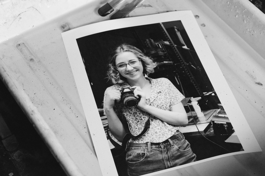 A portrait of Symon Knox developing with her camera in darkroom solution.
