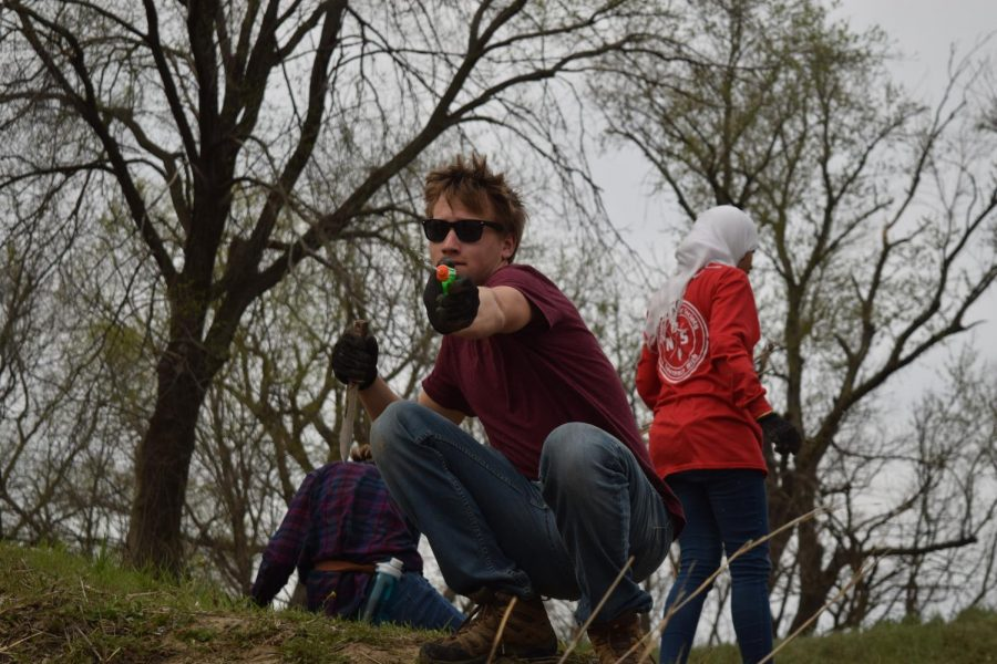 Senior Pierce Saturday shoots water gun while volunteering at the river clean up. Saturday is a member of Environmental Club, who participated with the River Restoration Project, run by Friends of the Kaw, on April 10th.