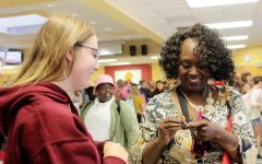 "At the Club Fair on Aug. 26, senior Megan Drumm gives interim principal Cynthia Johnson a pin reading ""You put the pal in principal."" Drumm got the pin on a visit to the Herff Jones yearbook plant earlier that day. ""I saw the pin and immediately thought of Mama J,"" Drumm said."