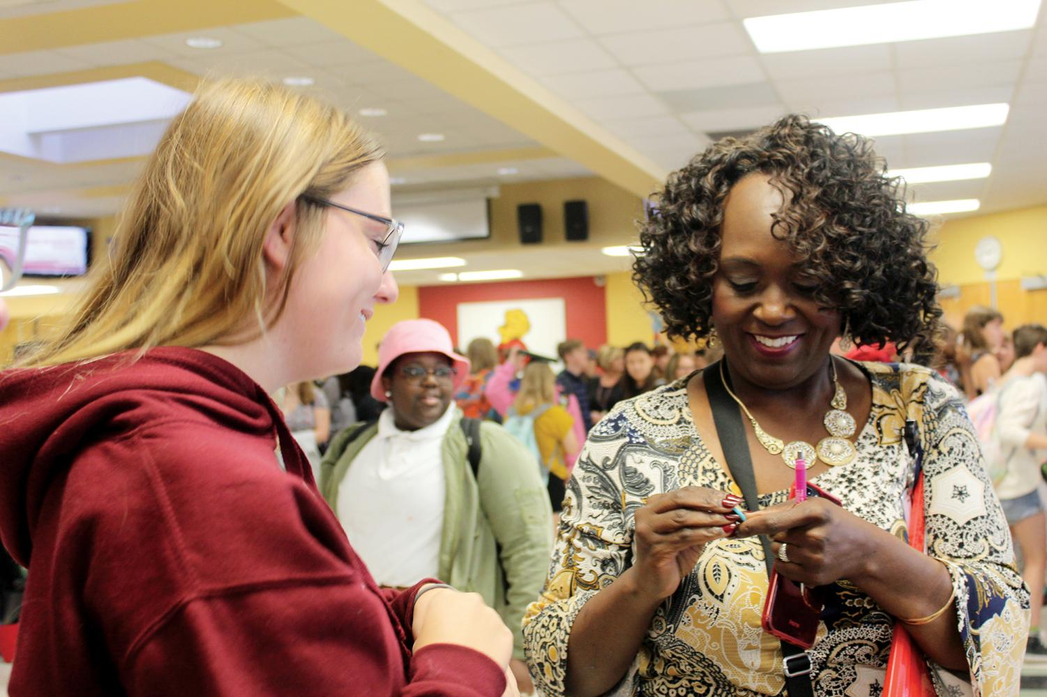 """At the Club Fair on Aug. 26, senior Megan Drumm gives interim principal Cynthia Johnson a pin reading """"You put the pal in principal."""" Drumm got the pin on a visit to the Herff Jones yearbook plant earlier that day. """"I saw the pin and immediately thought of Mama J,"""" Drumm said."""