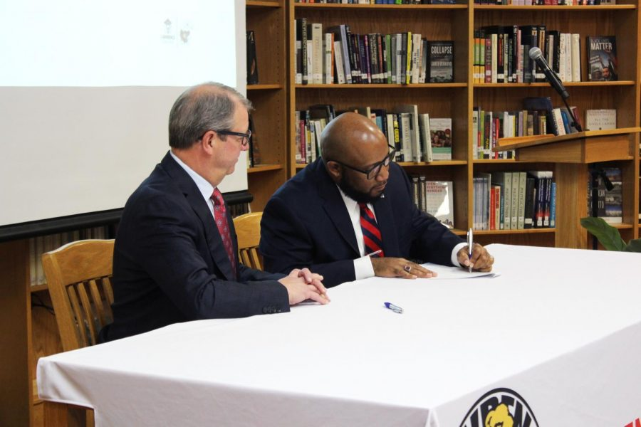 Chancellor Doug Girod (left) and district Superintendent Anthony Lewis (right) sign agreement