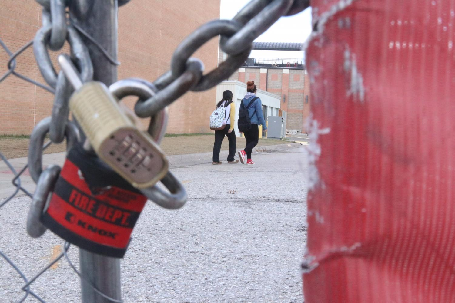 LOCKED DOWN — Behind the chain-linked fence, students make their way to class. New security measures have been implemented across the campus this year.