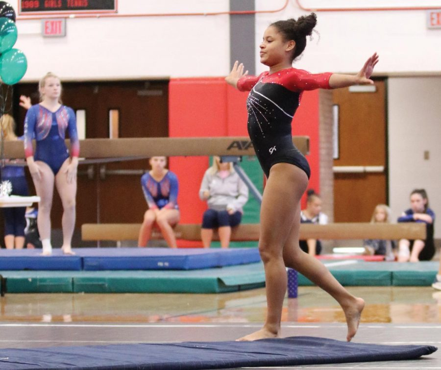 """Arms outstretched, sophomore Paris Spotted Tail performs her floor routine during a September home meet. Spotted Tail finished floor with a score of 8.95 to claim her second place spot. An overall gifted gymnast, Spotted Tail said she was especially invested in floor. """"I love it because I get to dance,"""" Spotted Tail said."""
