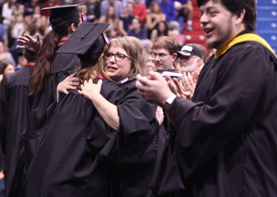 Teacher Valerie Schrag embraces a member of the class or 2019 during graduation in May last year. USD 497 on Monday night voted to reduce the number of credits needed to graduate as a result of the coronavirus pandemic, which will close schools through the end of the year although learning will continue online.