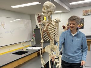 Anatomy teacher Jo Huntsinger packs up her classroom skeleton as Lawrence High closes its building for the remainder of the year