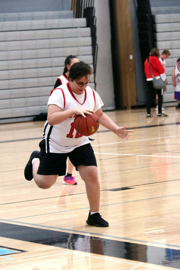 Determined, sophomore Anthony Watts dribbles down the court during the Nov. 2 Unified Basketball tournament at Shawnee Mission East. Being a part of Unified Sports for two years now, Watts has an understanding of his passion for sports.