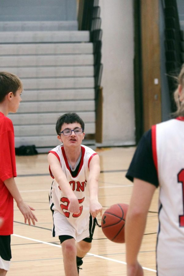 Competing, senior Mikey Ebenstein passes the ball to his teammate to try for a basket in his Unified Basketball game. The team fell just short of first place this season but that doesn't bother Ebenstein.
